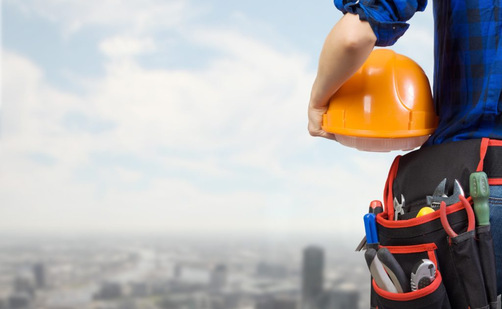 field technician looking out over a cityscape, holding a yellow hard hat